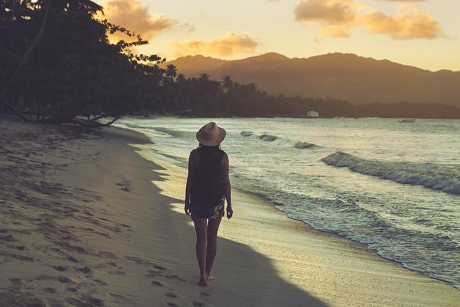 Traveler Girl Walking On Tropical Beach In Sunset. Vintage Photo