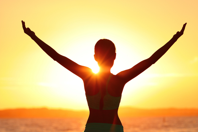 Freedom woman with open arms silhouette in sunrise against sun f